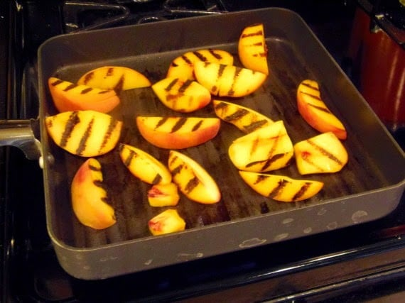 Peach slices with grill marks in a grill pan.