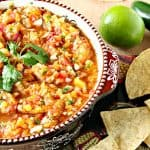Fresh peach salsa in a bowl with cilantro, chips, lime and jalapeno