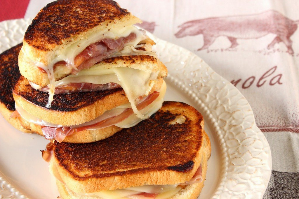 A horizontal photo of several halved prosciutto, melon, and provolone grilled cheese sandwiches on an oval platter.