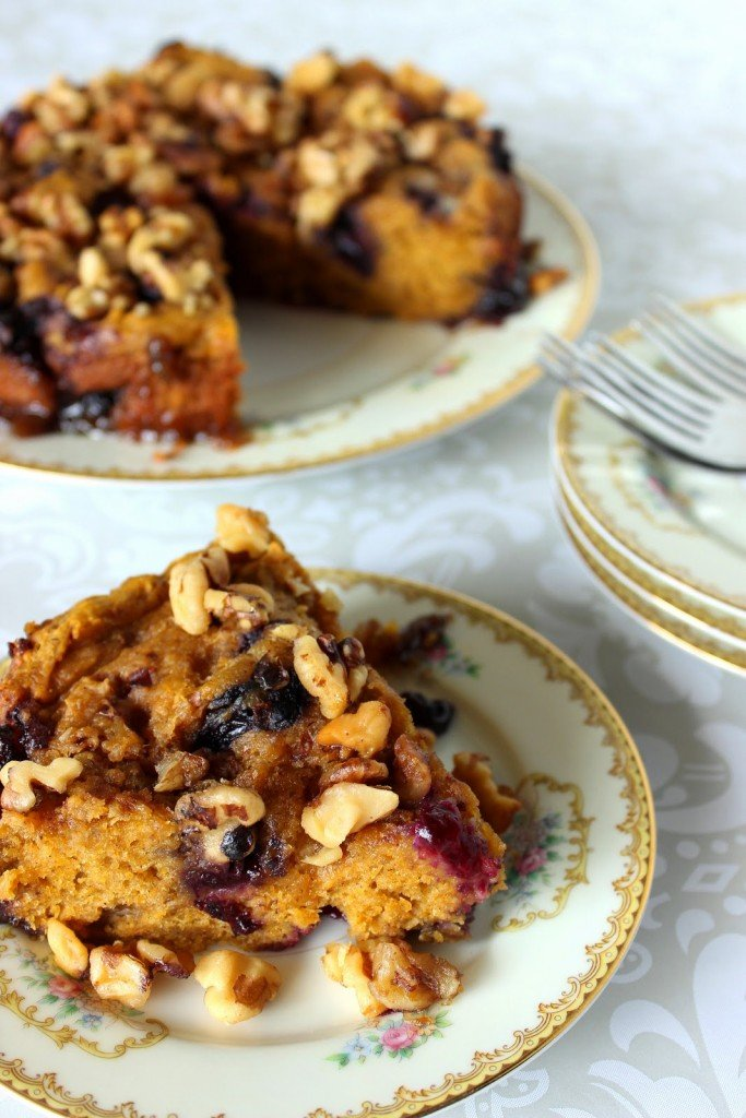 A vertical photo of a slice of Slow Cooker Pumpkin Blueberry Cake on a china plate.
