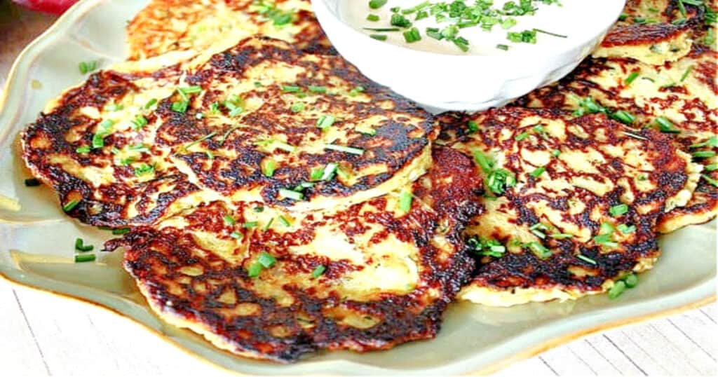 A plate filled with fried Spaghetti Squash and Zucchini Pancakes with chives as garnish.