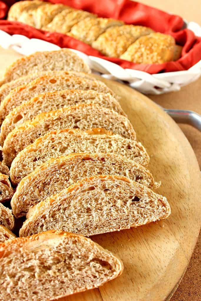 Vertical photo of slices of whole wheat French bread on a cutting board with a whole loaf in the background.