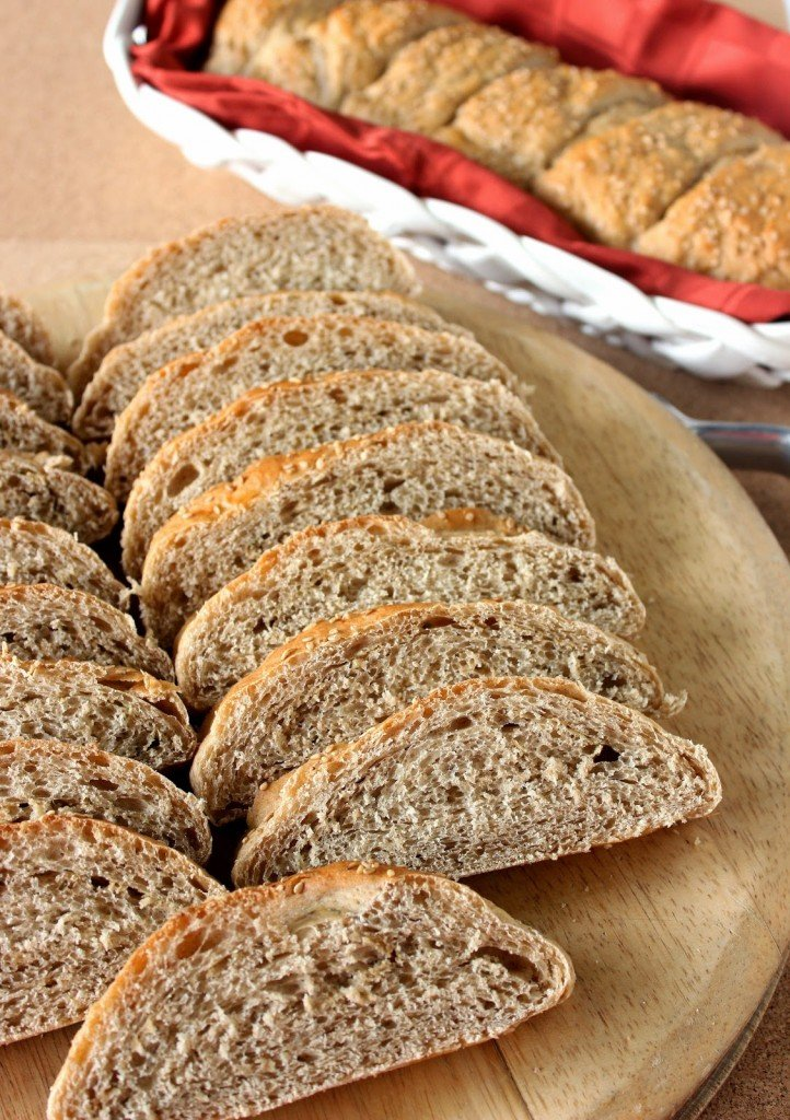 Vertical image of sliced whole wheat French bread on a cutting board.