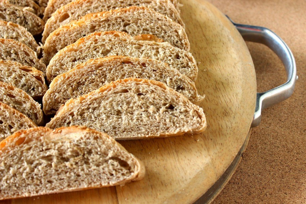 Closeup photo of whole wheat bread slices on a cutting board.
