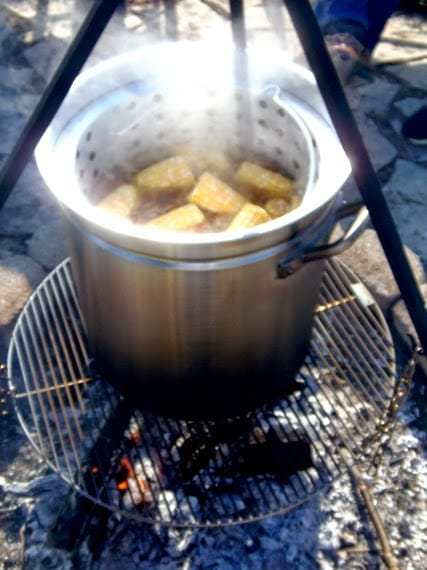 A huge steamy pot of low-country seafood boil being cooked over and outdoor firepit.