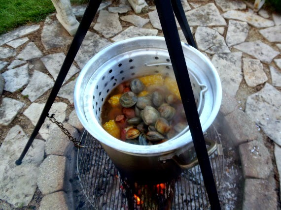 Looking inside of a huge pot of seafood and corn cooking over an outdoor firepit.