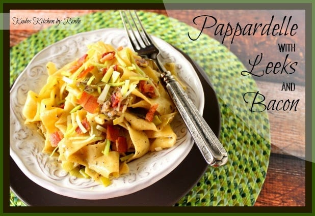 A horizontal framed title text photo of pappardelle pasta recipe with leeks and bacon in a while bowl on a green place mat with a fork.
