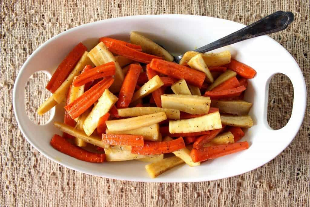 Overhead horizontal photo of an oval white dish with roasted carrots and parsnips and a serving spoon.