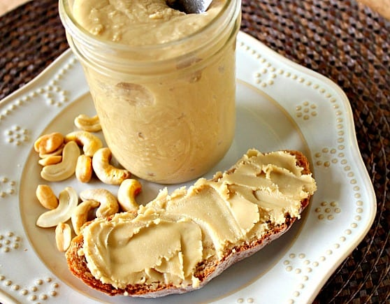 A slice of bread with spread with cashew peanut butter on a white plate with a jar.