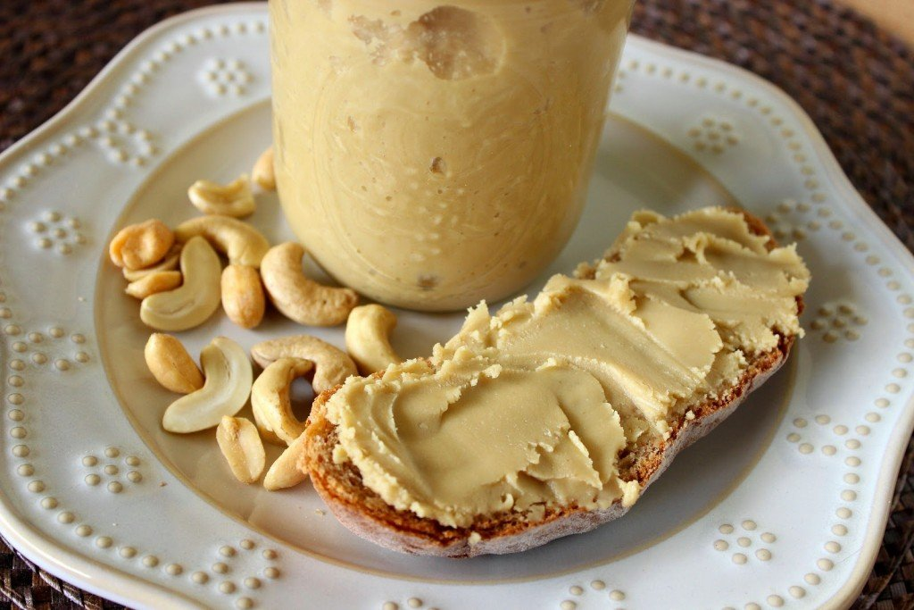 Healthy Honey Cashew Peanut Butter on a white plate with nuts and a jar.