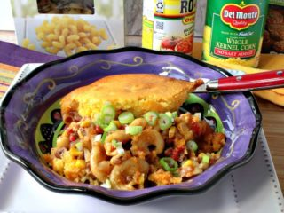A purple bowl filled with chili mac with a cornbread crust along with a spoon.