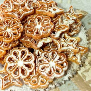 Fried Snowflake Rosette Cookies with Confectioners Sugar Dusting on a round glass platter.