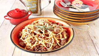 A bowl filled with Linguine with Lamb along with a fork and a stack of bowls in the background.