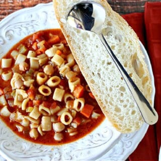 An offset horizontal photo of a bowl of Tuscan Pasta Soup with a slice of bread and a spoon on the side.