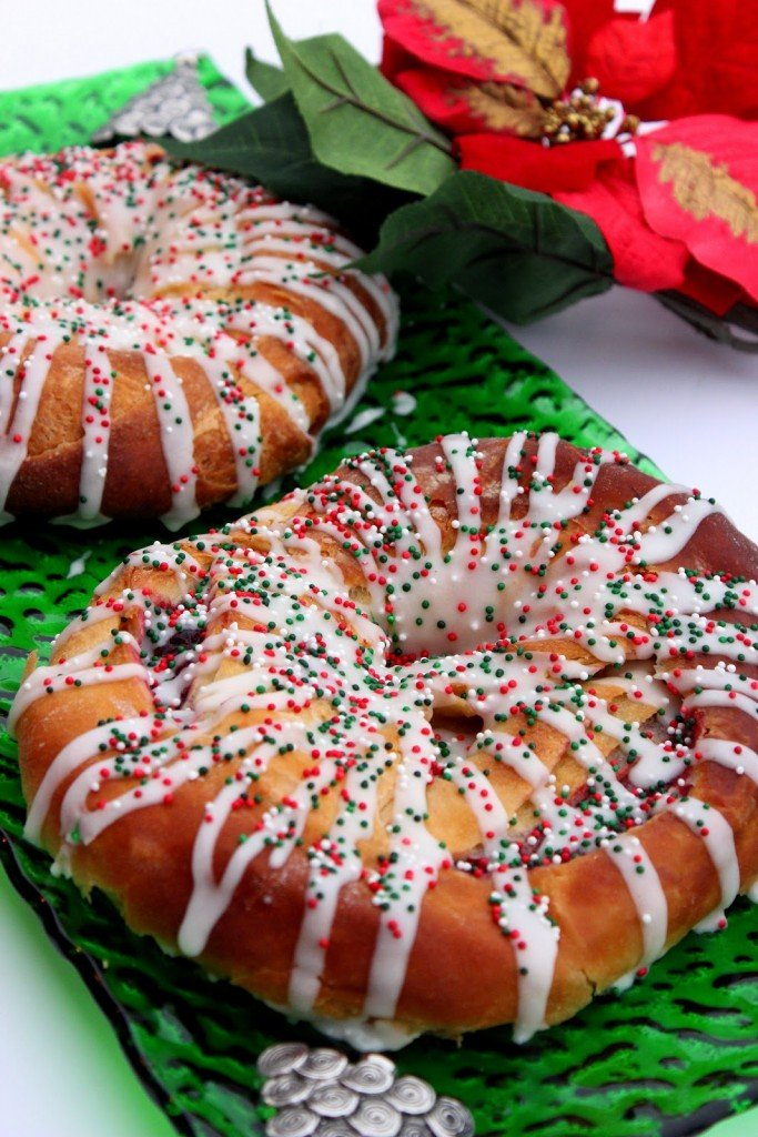 A vertical image of two cranberry Kringles on a green Christmas platter with icing and Christmas sprinkles.