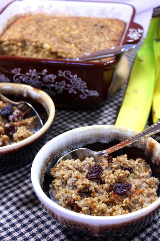 Long vertical image of baked steel cut oatmeal in brown bowls with spoons and bananas in the background.