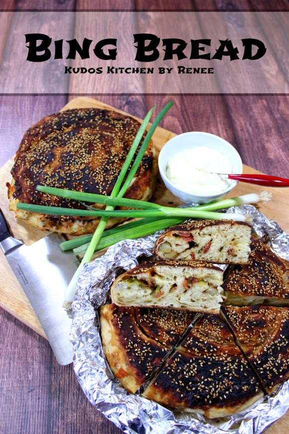 A vertical photo of two loaves of bing bread on a wooden board with scallions.