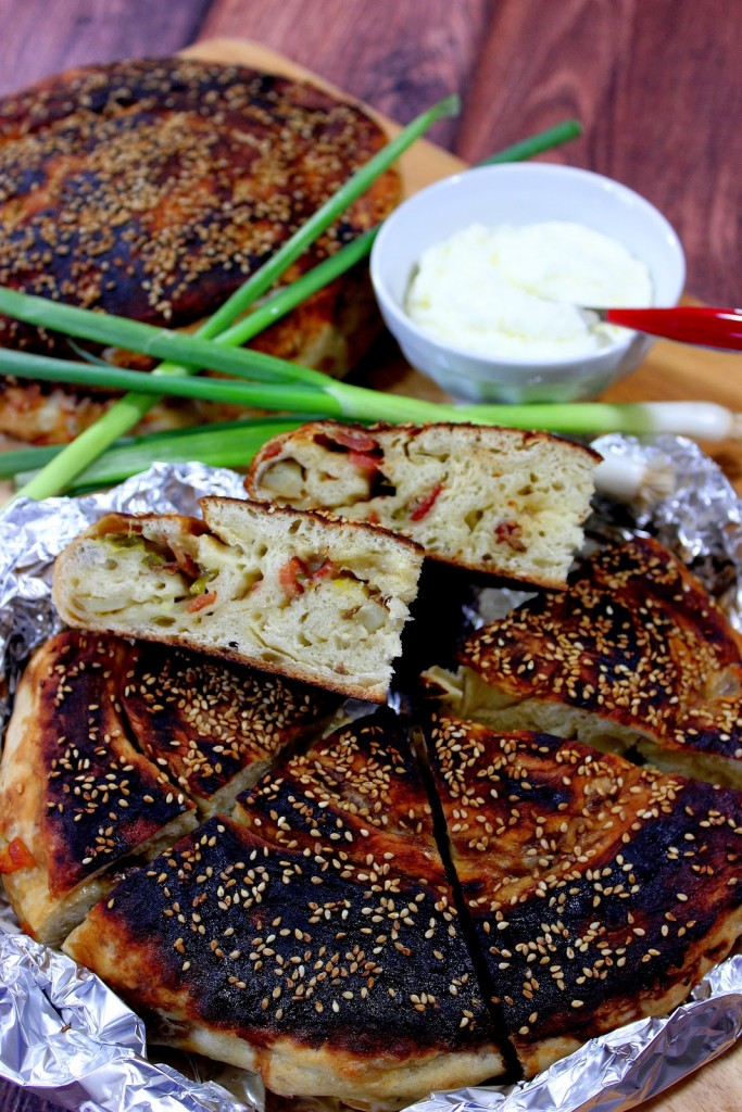 A closeup vertical image of the inside of Chinese Bing Bread with Bacon, scallions, and sesame seeds.