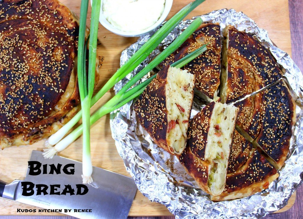 Overhead photo of Chinese Bing Bread in foil with scallions and a cleaver.