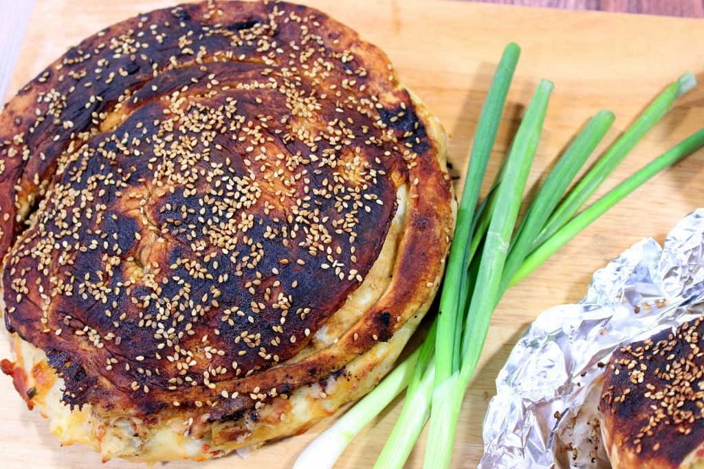 Overhead photo of a Chinese bing bread with sesame seeds and scallions.