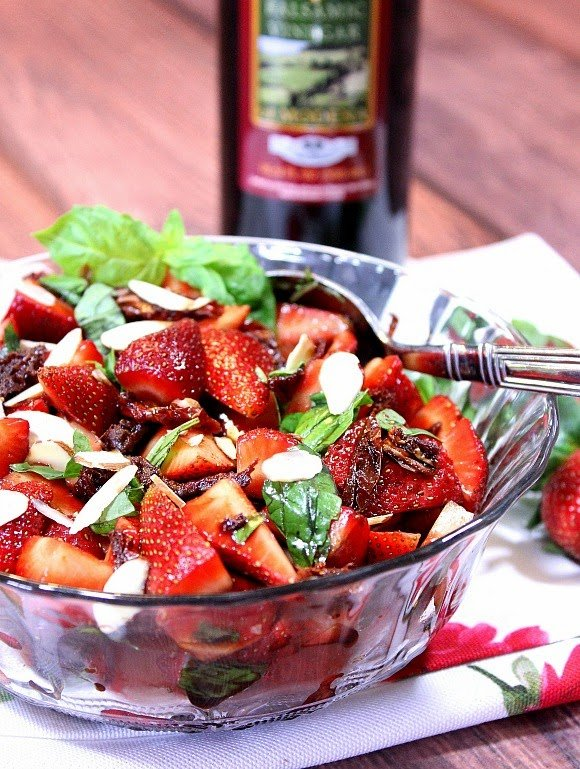 A glass bowl of strawberry basil salad. A jar of balsamic vinegar is in the background
