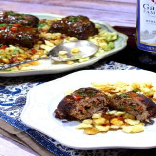 A plate of German beef rouladen in the foreground and a platter of German beef rouladen in the background with a bottle of wine