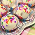 Closeup photo of no-bake shortbread cookie truffles with white chocolate and multi-colored sprinkles