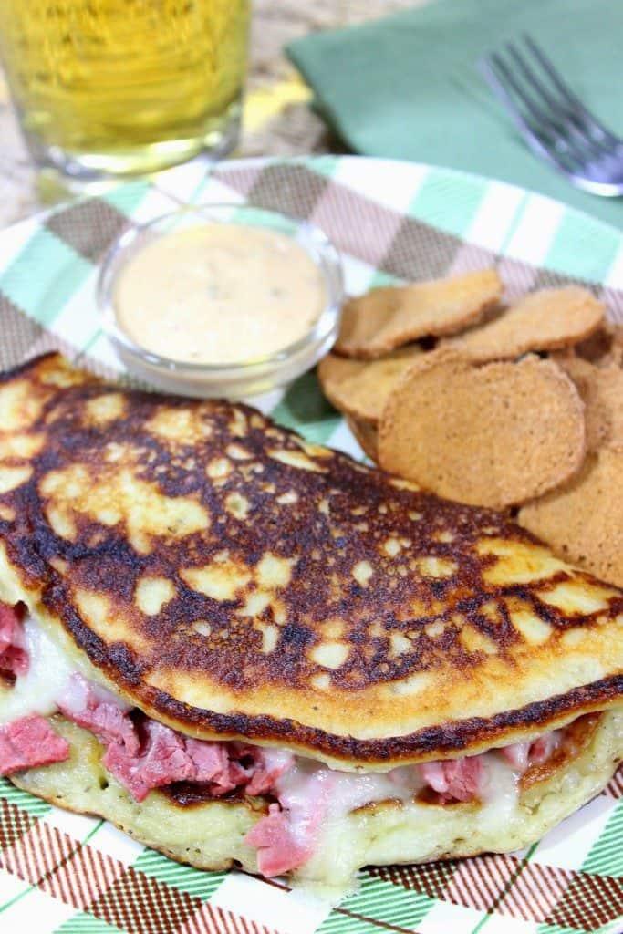 Irish Stuffed Boxty potato pancake with corned beef and melted Swiss cheese on a plaid plate