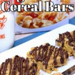 Closeup image of tiger paws cereal bars on a white plate with a knife with peanut butter in the foreground.