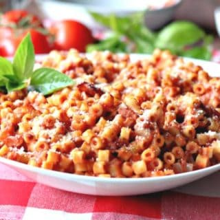 A large bowl of bacon tomato pasta with fresh basil and tomatoes in the background