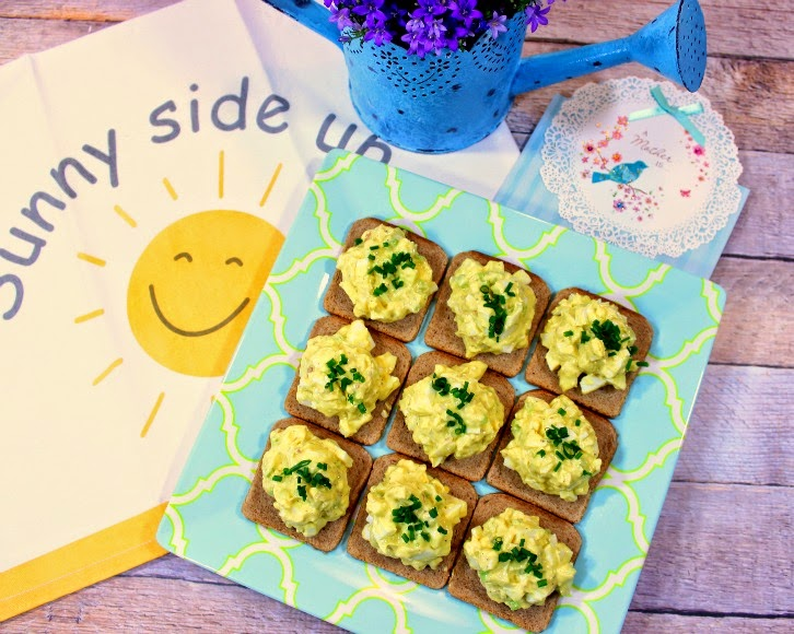 Overhead picture of a square plate of egg salad appetizers with a smiling face sunshine napkin and a blue watering can with purple flowers.