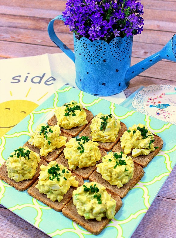 Plate of egg salad appetizers with a blue watering can and purple flowers in the background