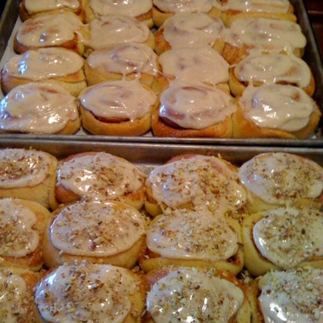 Two trays of homemade iced cinnamon rolls. One with nuts and one without.