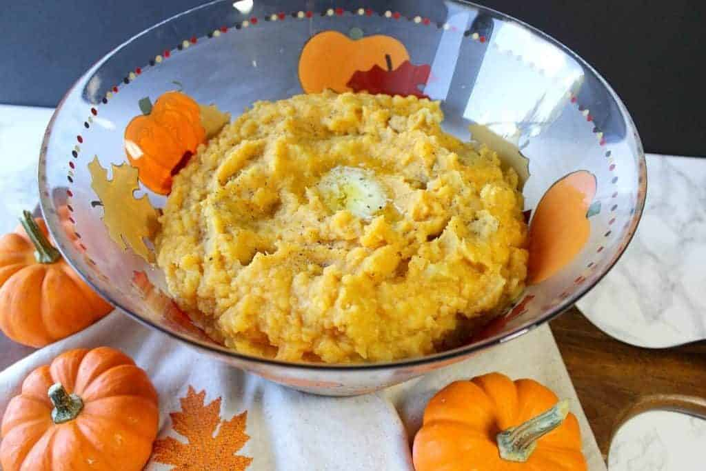 Pumpkin Mashed Potatoes in a hand painted glass bowl with mini pumpkins.