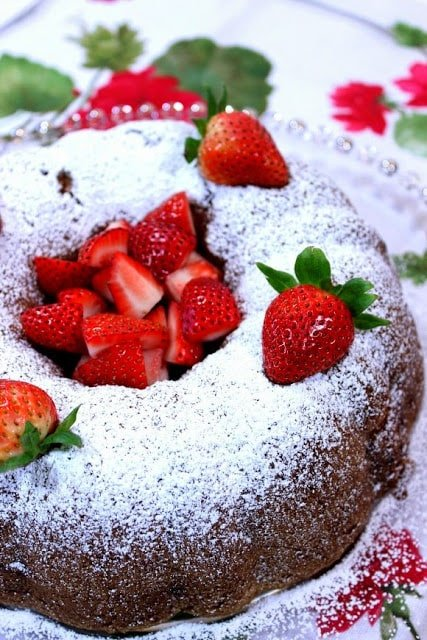 Vertical closeup photo of a bundt cake on a glass plate with fresh strawberries on top and a confectioners sugar dusting.