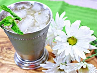 A Traditional Mint Julep in a metal cocktail glass with fresh mint and white daisies on the side.