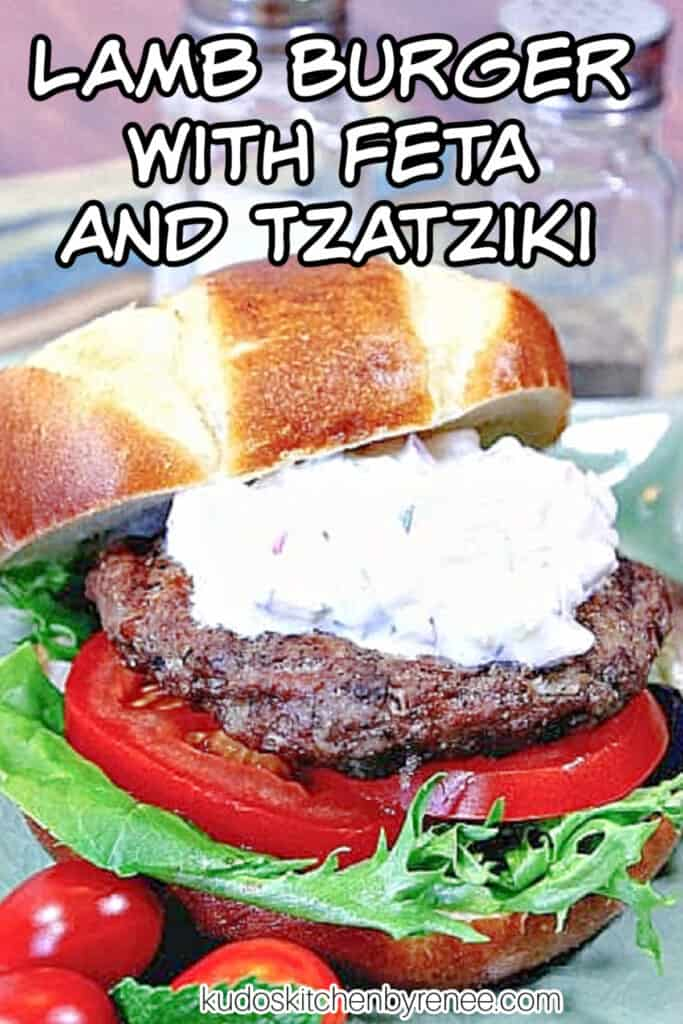 A closeup vertical image of a Lamb Burgers with Feta and Tzatziki along with a title text overlay graphic with some tomato and lettuce.