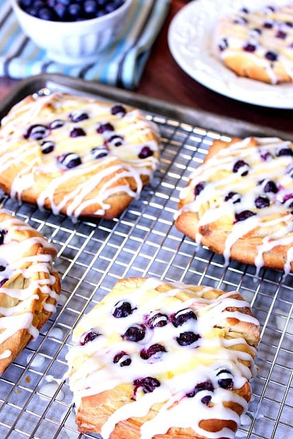 Vertical photo of a baking sheet filled with homemade blueberry cheese Danish.