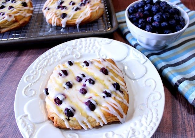 Blueberry cheese danish on a white plate with a bowl of fresh blueberries in the background.