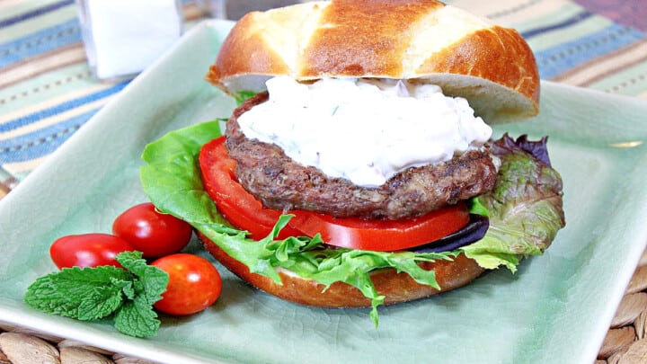 A Greek Lamb Burger with Feta and Tzatziki on a green square plate with tomato and lettuce.
