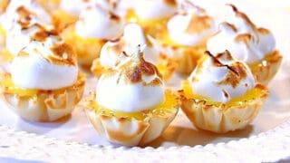 A closeup horizontal photo of a plate of Lemon Meringue Tartlets with a toasted meringue.