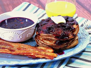 A stack of Whole Wheat Blueberry Pancakes on a blue platter with bacon and a bowl of Blueberry Maple Syrup on the side.