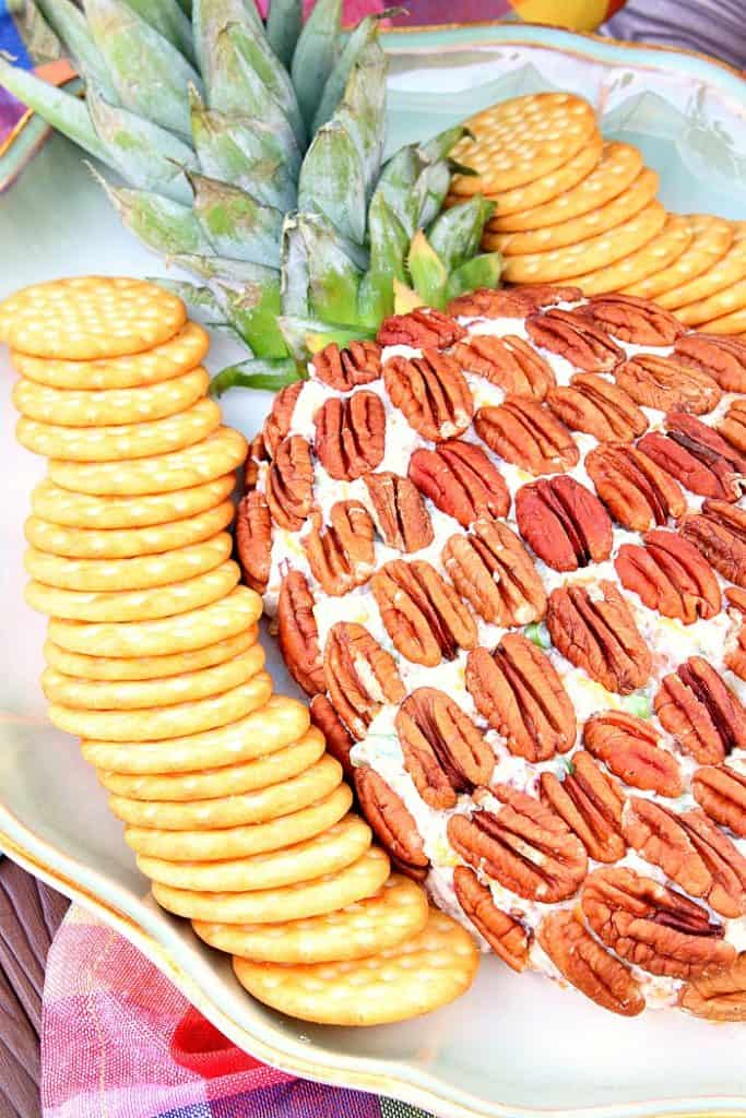Closeup photo of a pineapple cheese ball with pecans and crackers
