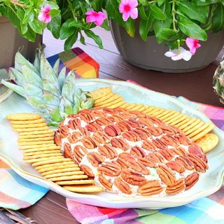 pineapple cheeseball on a platter with crackers and flowers in the background