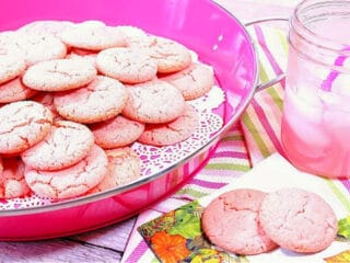 A pink tray filled with Pink Lemonade Cookies along with a glass of pink lemonade on the side.