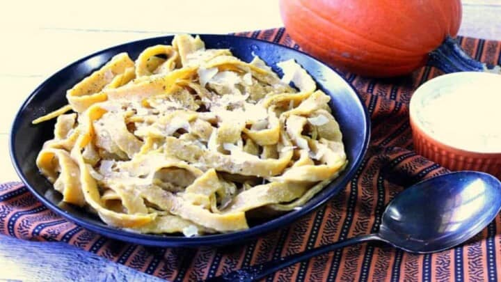 A black bowl filled with homemade pumpkin pasta with sage and a small real pumpkin in the background