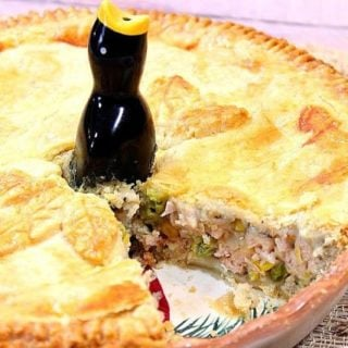 A whole Pork Pot Pie with a slice taken out and a pie bird in the center.