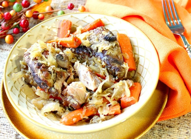 German Pork Ribs and Sauerkraut in a bowl with an orange napkin.