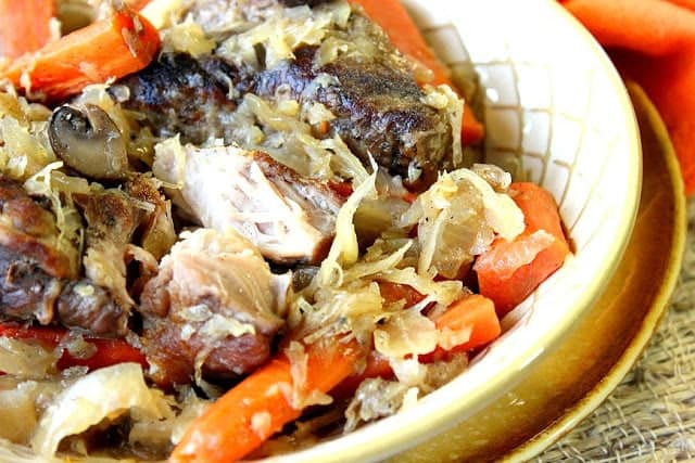 Closeup photo of a bowl of German Pork Ribs and Sauerkraut with carrots and mushrooms.