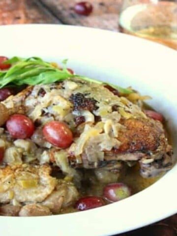 A white bowl filled with Riesling braised chicken thighs, red grapes and fresh tarragon.
